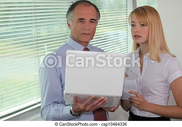 Businessman looking at a laptop with his assistant - csp10464336