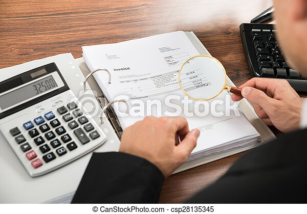 Businessman Looking At Invoice Through Magnifying Glass - csp28135345