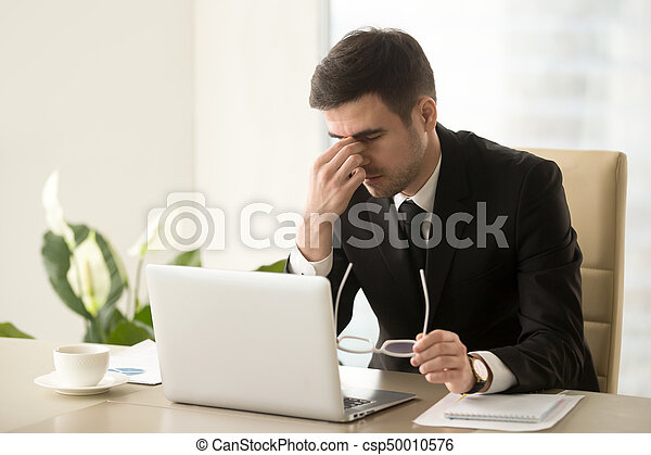 Businessman massaging nose bridge, holding glasses, eye strain, - csp50010576