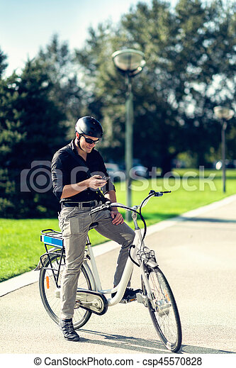Businessman on electric bicycle typing on cell phone - csp45570828