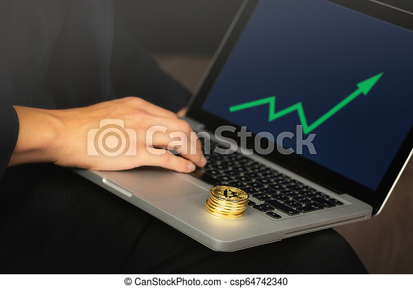 Businessman on laptop with bitcoin coins - csp64742340