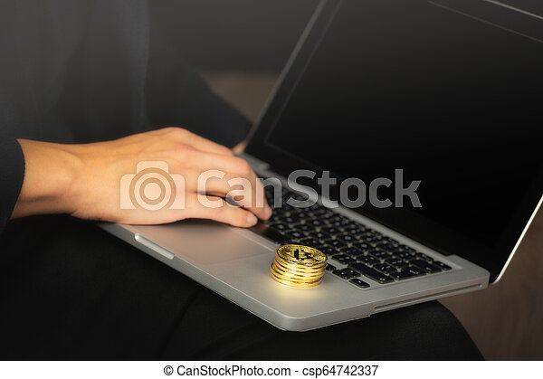 Businessman on laptop with bitcoin coins - csp64742337