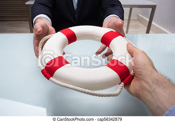 Businessman Passing Lifebuoy To His Partner - csp56342879