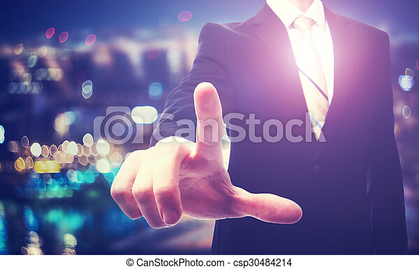 Businessman pointing to something on a blurred background - csp30484214