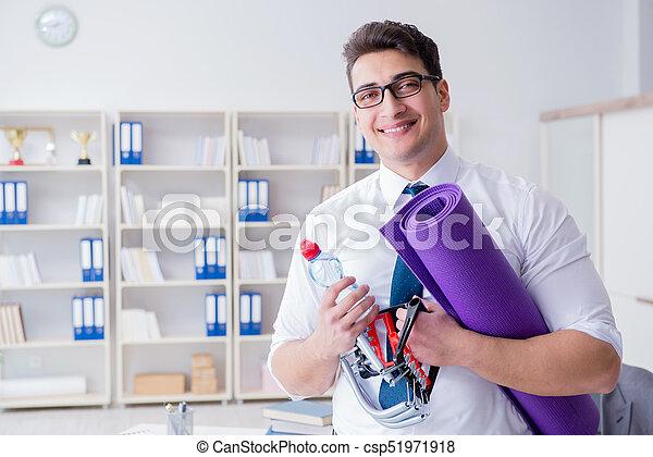 Businessman preparing to go exercising in gym - csp51971918