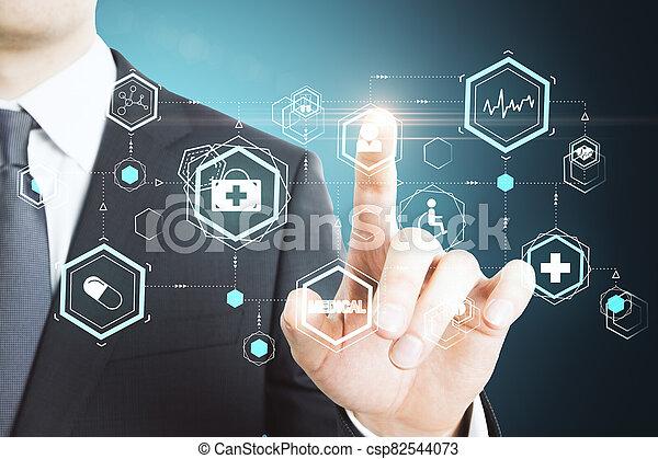 Businessman pushing creative glowing medical interface hud hologram. - csp82544073