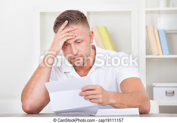 Businessman reacting in shock to a letter - csp19111157