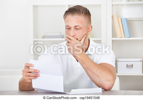 Businessman reacting in shock to a letter - csp19451548