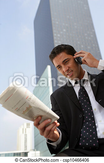 Businessman reading a newspaper in the city - csp10466406