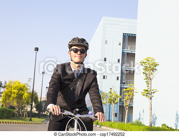 businessman riding a bicycle to workplace for protecting environment - csp17492252