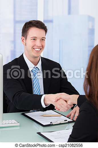 Businessman Shaking Hand Of Female Candidate - csp21082556