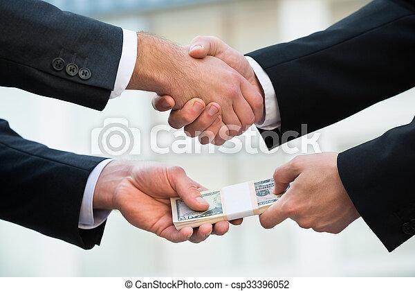 Businessman Shaking Hand While Bribing Partner - csp33396052