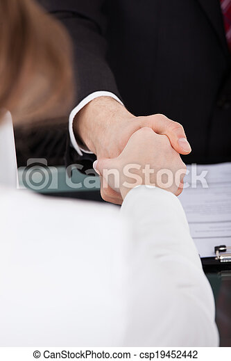 Businessman Shaking Hand With Female Candidate - csp19452442