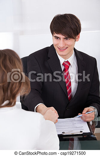 Businessman Shaking Hand With Female Candidate - csp19271500