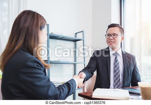 Businessman shaking hand with businesswoman in office - csp51365376