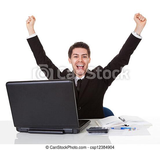 Businessman sitting at his desk rejoicing - csp12384904
