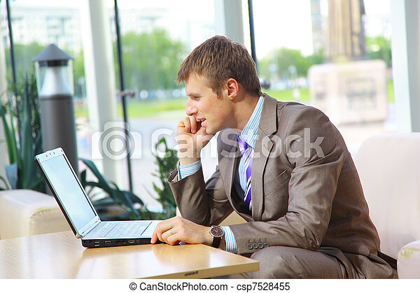 Businessman sitting at table in office hall, talking on mobile phone and using laptop computer  - csp7528455