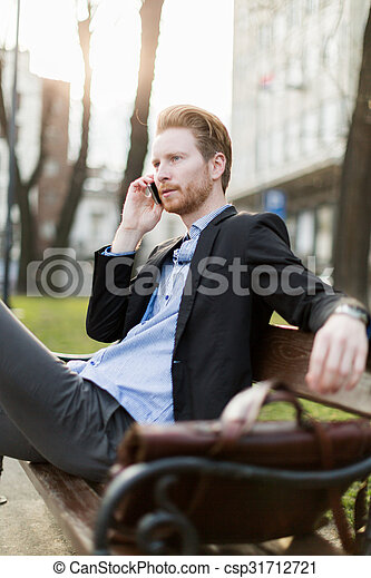 Businessman sitting on a bench and talking on the phone on a sunny day - csp31712721
