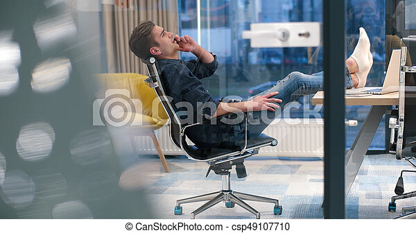 businessman sitting with legs on desk - csp49107710