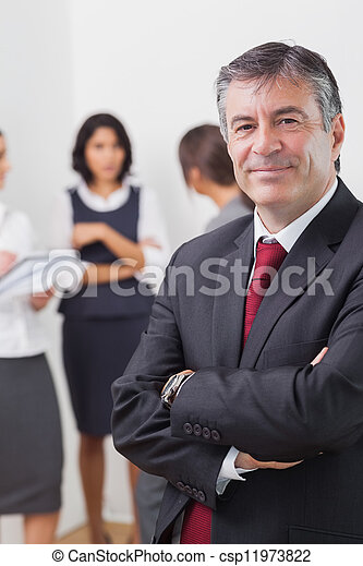 Businessman smiling with arms crossed and three businesswomen speaking in the background - csp11973822