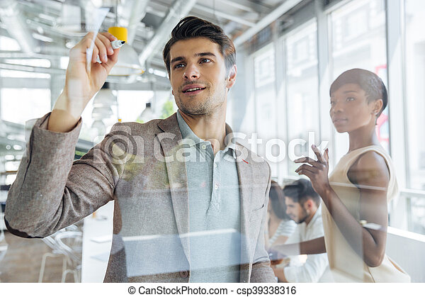 Businessman standing and writing on transparent board in office - csp39338316