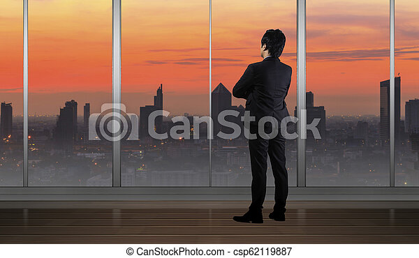 Businessman standing in Office building looking at Cityscape skyline night light - csp62119887