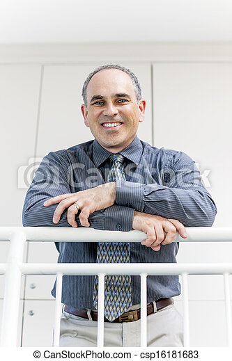 Businessman standing in office hallway smiling - csp16181683