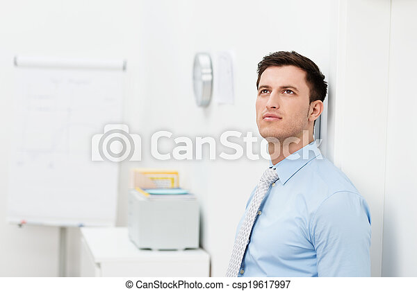 Businessman standing in the office thinking - csp19617997