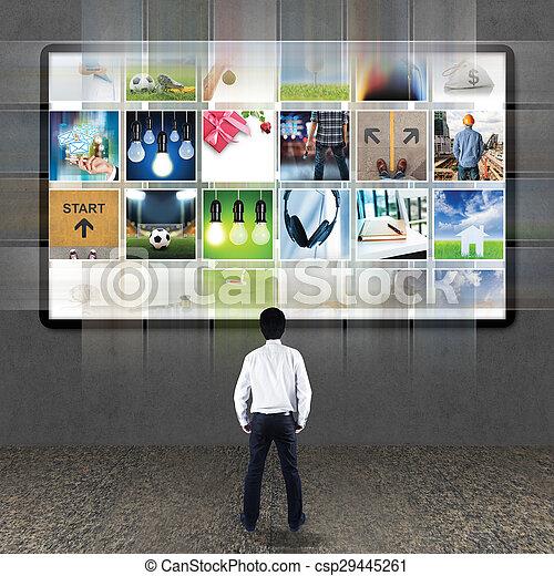Businessman standing looking at TV screen - csp29445261