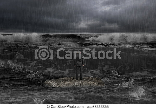 rear view businessman standing on rock facing oncoming waves with