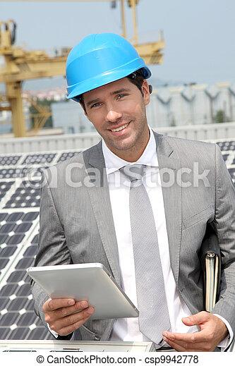 Businessman standing on solar panel installation - csp9942778