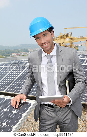 Businessman standing on solar panel installation - csp9941474