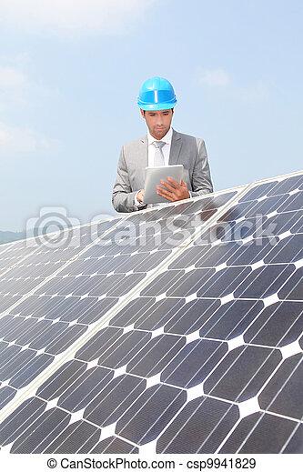 Businessman standing on solar panel installation - csp9941829