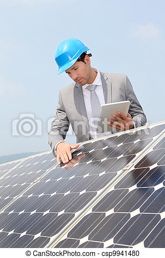 Businessman standing on solar panel installation - csp9941480