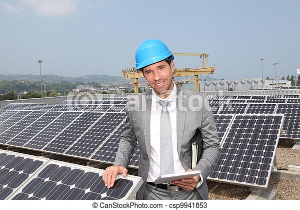 Businessman standing on solar panel installation - csp9941853