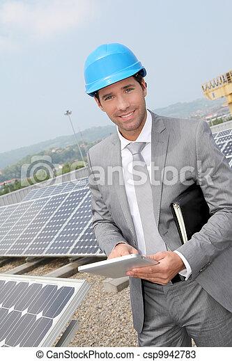 Businessman standing on solar panel installation - csp9942783