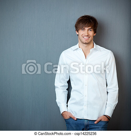 Businessman Standing With Hands In Pockets Against Blue Wall - csp14225236