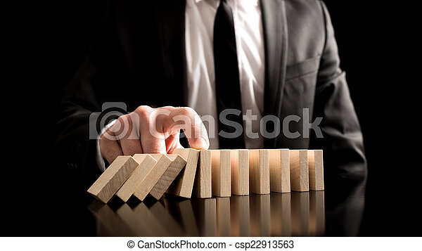 Businessman Stopping the Domino Effect - csp22913563