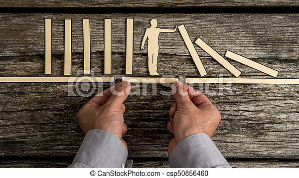 Businessman stopping the domino effect - csp50856460