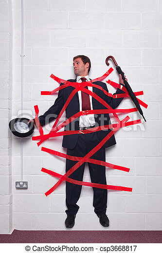 Businessman stuck to wall with red tape - csp3668817