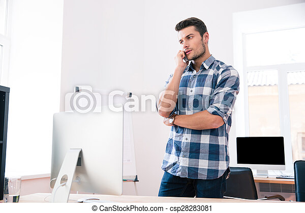 Businessman talking on the phone in office - csp28283081