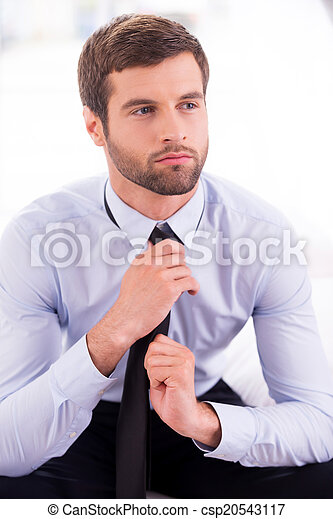 Businessman tying a necktie. Thoughtful young businessman tying a necktie while sitting on the bed  - csp20543117