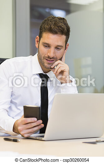 Businessman typing a message on mobile phone in office - csp30260054