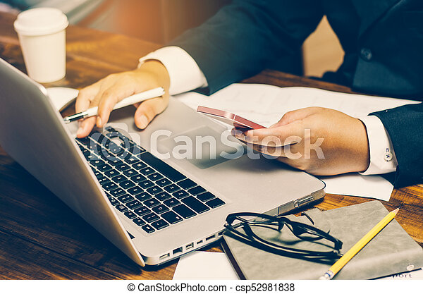 Businessman using credit card with a laptop to purchase on line - csp52981838