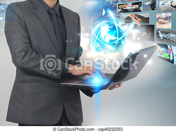 Businessman using laptop with glowing globe.Business connection concept. - csp40232353