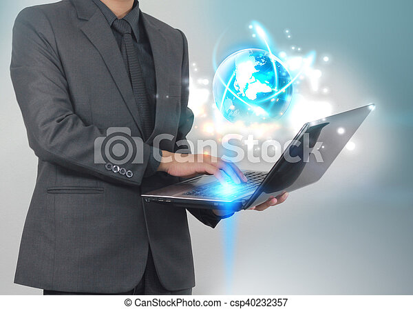Businessman using laptop with glowing globe.Business connection concept. - csp40232357