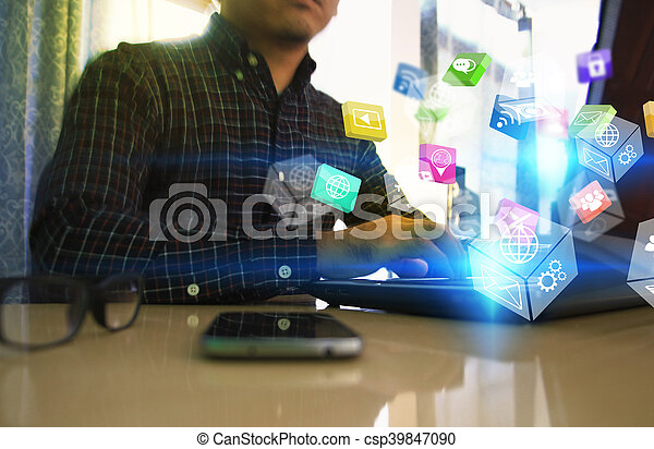 Businessman using laptop with social icons. - csp39847090
