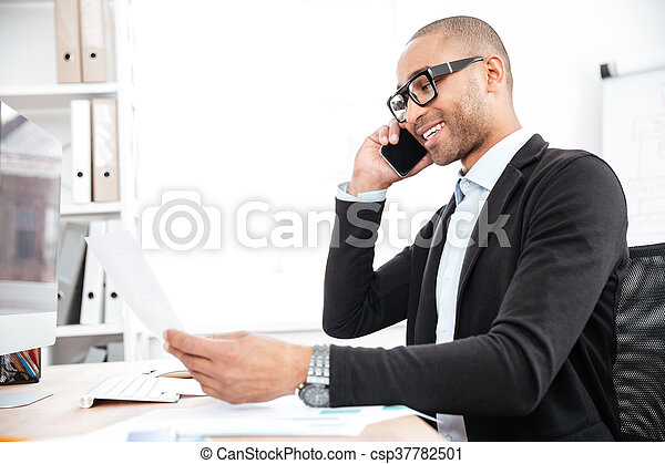 Businessman using mobile phone and looking at documents - csp37782501