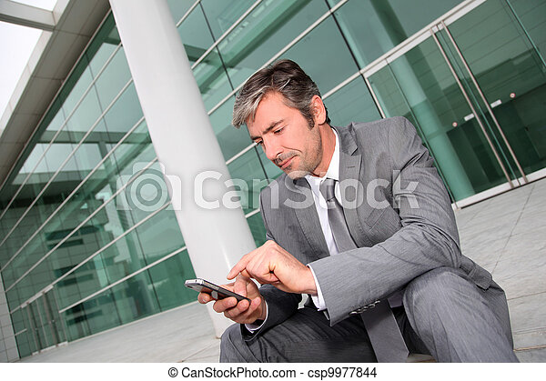 Businessman using mobile phone while seated in stairs - csp9977844