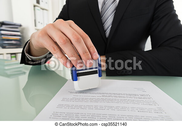 Businessman Using Stamper On Document - csp35521140